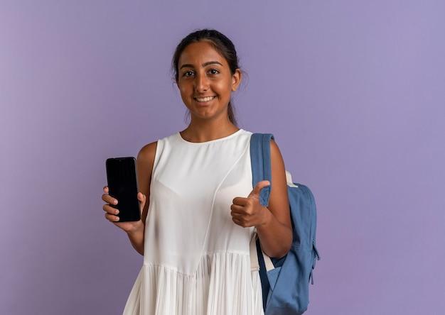 Улыбающаяся молодая школьница в сумке на спине держит телефон большим пальцем на фиолетовом