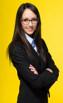 Smiling young secretary on yellow
