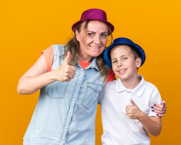 Smiling young slavic boy with blue party hat standing with his mother wearing purple party hat thumbing up isolated on orange wall with copy space