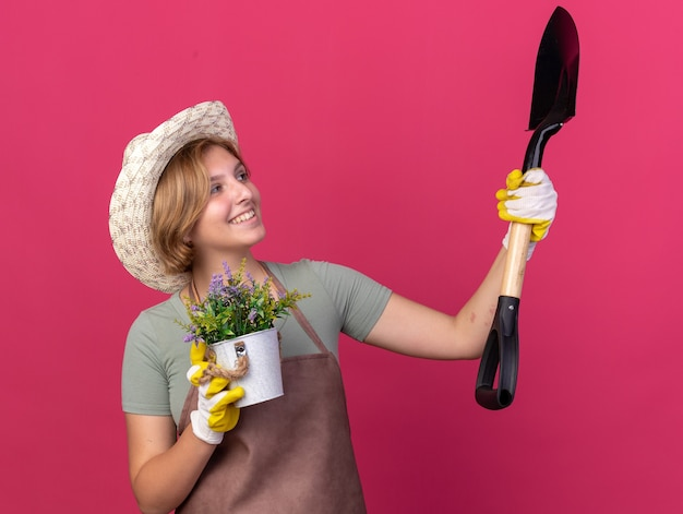 웃고 있는 젊은 슬라브 여성 정원사는 원예용 모자와 장갑을 끼고 화분에 꽃을 들고 복사 공간이 있는 분홍색 벽에 격리된 스페이드를 바라보고 있습니다.