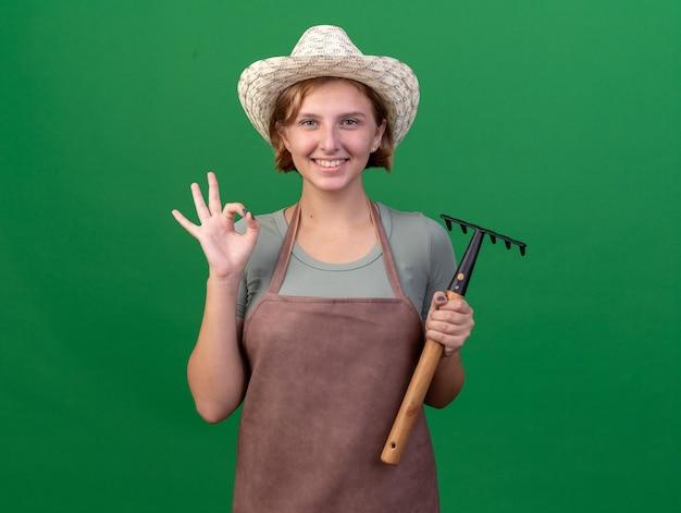 확인 서명 몸짓과 녹색 갈퀴를 들고 원예 모자를 쓰고 웃는 젊은 슬라브 여성 정원사
