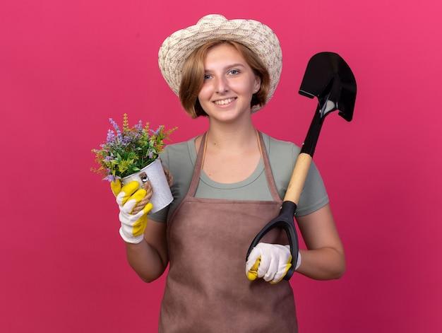 Sorridente giovane giardiniere femmina slava che indossa cappello da giardinaggio e guanti che tengono fiori in vaso di fiori e vanga isolati sulla parete rosa con spazio di copia