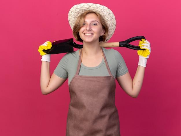 Sorridente giovane giardiniere femmina slava che indossa cappello da giardinaggio e guanti che tengono la vanga dietro il collo isolata sulla parete rosa con spazio per le copie