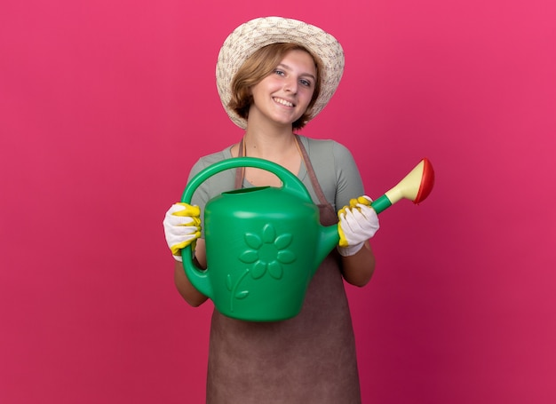 Smiling young slavic female gardener wearing gardening hat and gloves holding watering can isolated on pink wall with copy space