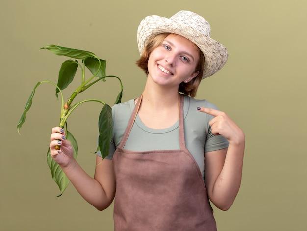 Улыбающаяся молодая славянская женщина-садовник в садовой шляпе держит и указывает на растение на оливково-зеленом