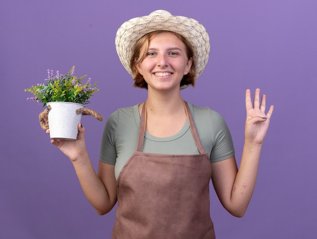 Smiling young slavic female gardener wearing gardening hat holding flowers in flowerpot and gesturing four with fingers on purple