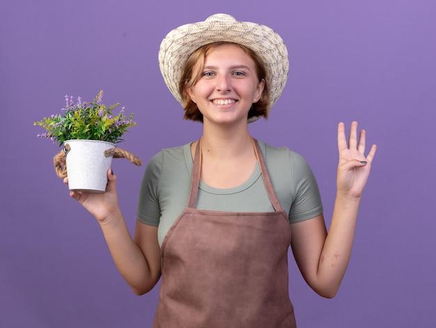 植木鉢に花を保持し、紫色の指で4つを身振りで示す園芸帽子をかぶって若いスラブの女性の庭師を笑顔