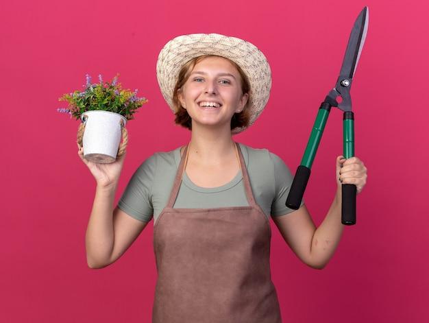 Sorridente giovane femmina slava giardiniere che indossa cappello da giardinaggio tenendo forbici da giardinaggio e fiori in vaso di fiori isolato sulla parete rosa con spazio di copia