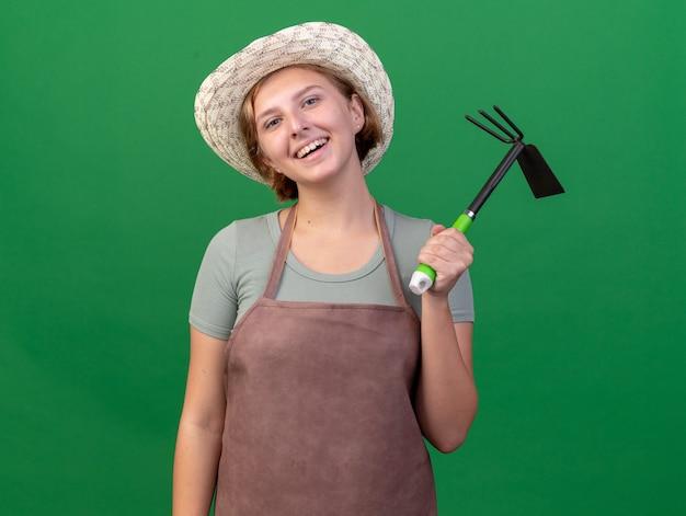 Улыбающаяся молодая славянская женщина-садовник в садовой шляпе держит грабли на зеленом