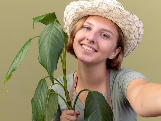 Sorridente giovane giardiniere femmina slava che indossa cappello da giardinaggio tenendo la pianta e fingendo di tenere la macchina fotografica prendendo selfie