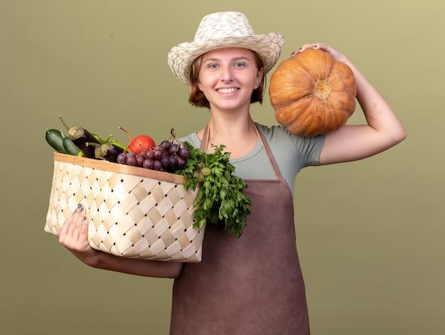 올리브 그린에 어깨에 야채 바구니와 호박을 들고 원예 모자를 쓰고 웃는 젊은 슬라브 여성 정원사