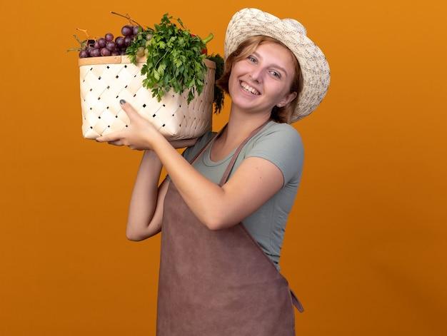 Sorridente giovane giardiniere femmina slava che indossa un cappello da giardinaggio tiene un cesto di verdure isolato su una parete arancione con spazio di copia