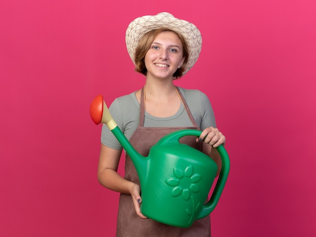 Smiling young slavic female gardener wearing gardening hat holds watering can