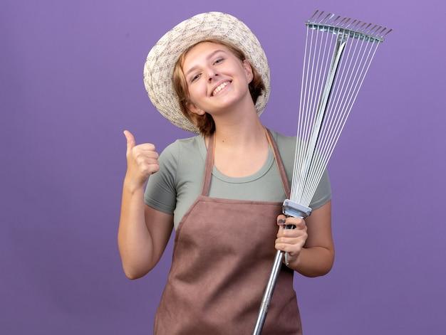 원예 모자를 쓰고 웃는 젊은 슬라브 여성 정원사 엄지 손가락과 보라색 잎 갈퀴 보유