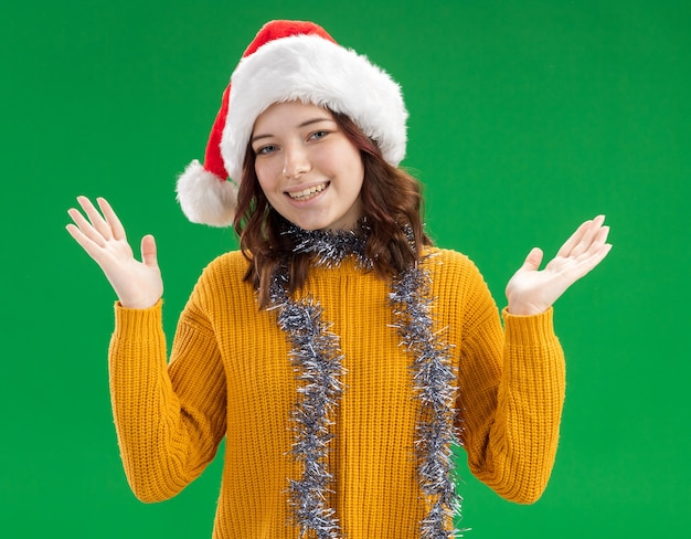 サンタの帽子とコピースペースで緑の壁に分離された手を開いて手を握って首の周りに花輪と笑顔の若いスラブの女の子