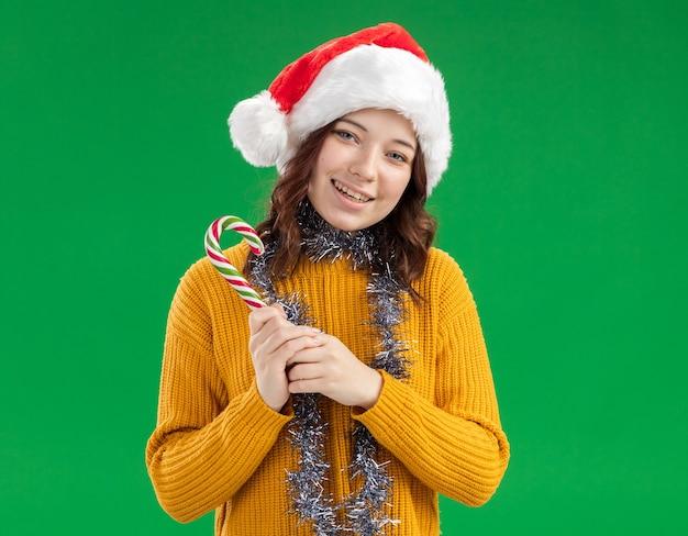 Улыбающаяся молодая славянская девушка в новогодней шапке и с гирляндой на шее держит конфету, изолированную на зеленом фоне с копией пространства