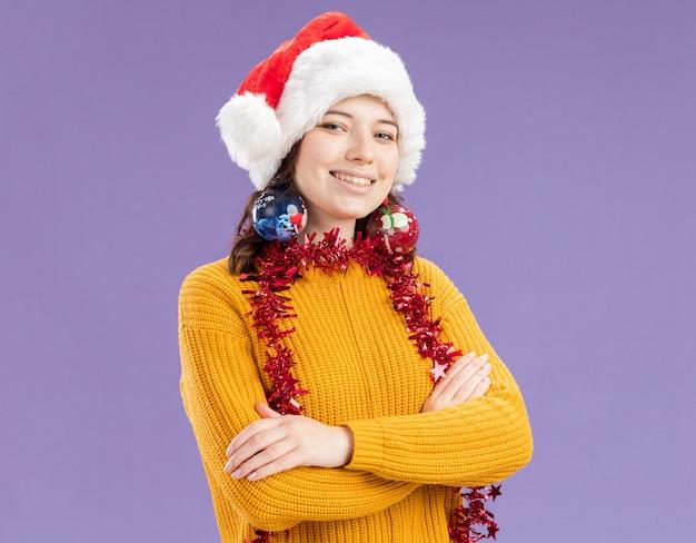 サンタの帽子と首に花輪を持つ笑顔の若いスラブの女の子は、コピースペースと紫色の壁に分離された交差した腕で立っている耳にガラス玉の飾りを保持します