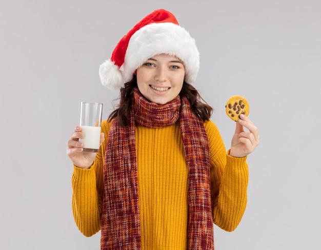 サンタの帽子と首の周りのスカーフと笑顔の若いスラブの女の子は、コピースペースと白い背景で隔離の牛乳とビスケットのガラスを保持します。