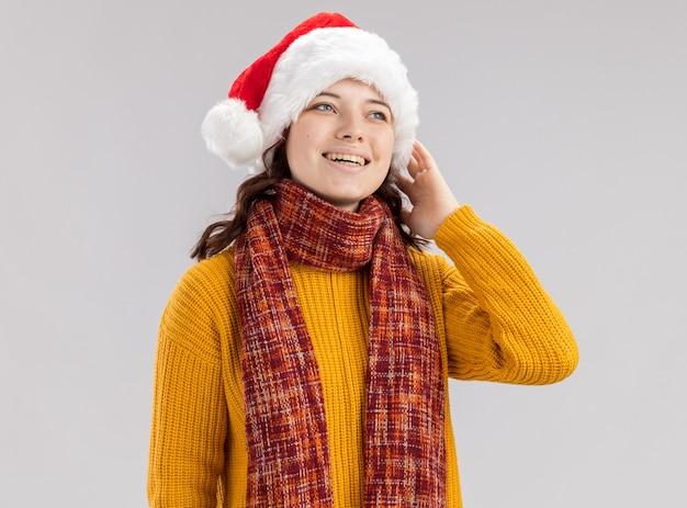 Улыбающаяся молодая славянская девушка в новогодней шапке и с шарфом на шее кладет руку на лицо и смотрит на сторону, изолированную на белой стене с копией пространства