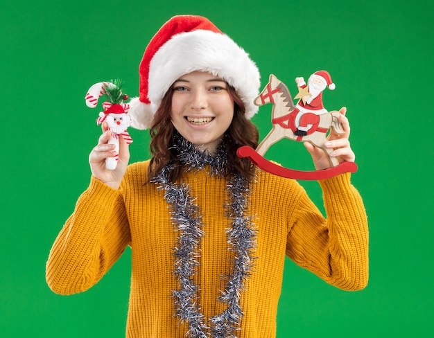 Smiling young slavic girl with santa hat and with garland around neck holding candy cane and santa on rocking horse decoration isolated on green wall with copy space