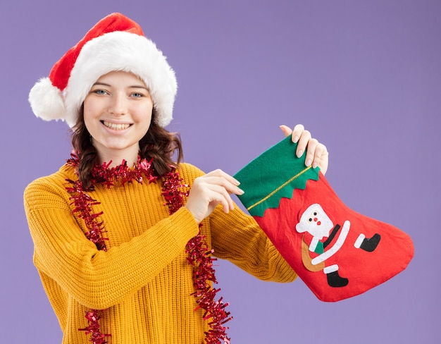 Smiling young slavic girl with santa hat and with garland around neck holding christmas stocking isolated on purple background with copy space