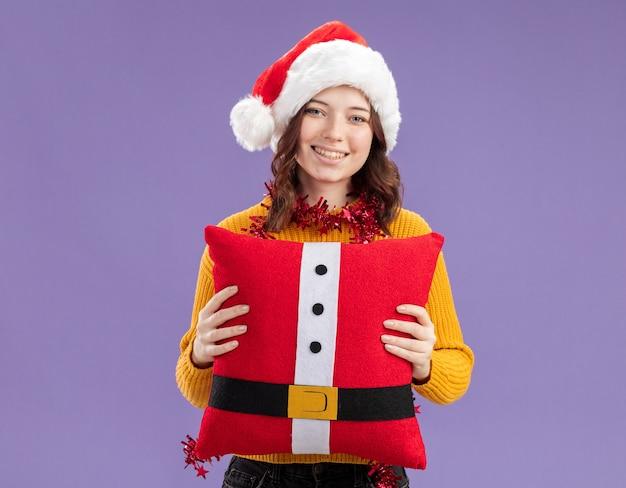 Sorridente giovane ragazza slava con cappello da babbo natale e con ghirlanda intorno al collo che tiene cuscino decorato isolato su parete viola con spazio copia