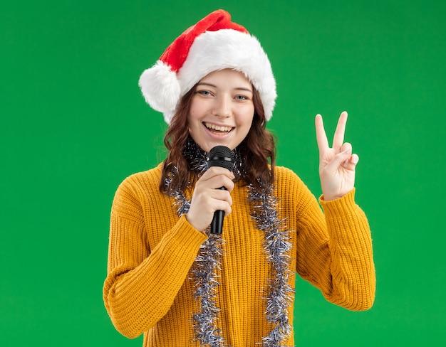 Sorridente giovane ragazza slava con cappello santa e con ghirlanda intorno al collo tenendo il microfono e gesticolando segno di vittoria
