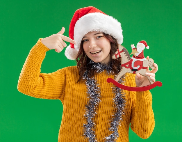 Smiling young slavic girl with santa hat and with garland around neck holding and pointing at santa on rocking horse decoration isolated on green wall with copy space