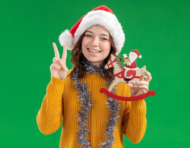Smiling young slavic girl with santa hat and with garland around neck holding santa on rocking horse decoration and gesturing victory sign