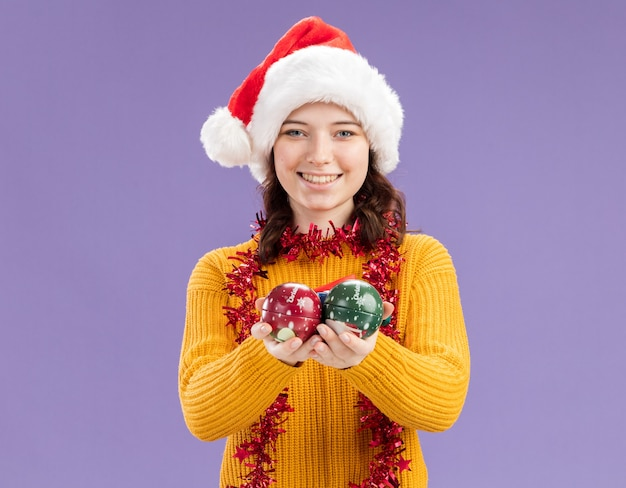 Smiling young slavic girl with santa hat and with garland around neck holds glass ball ornaments isolated on purple wall with copy space