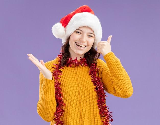 Sorridente giovane ragazza slava con santa hat e con ghirlanda intorno al collo pollice in alto e tiene la mano aperta isolata su sfondo viola con spazio di copia