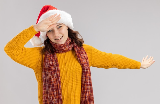 Smiling young slavic girl with santa hat and with scarf around neck doing dab isolated on white wall with copy space