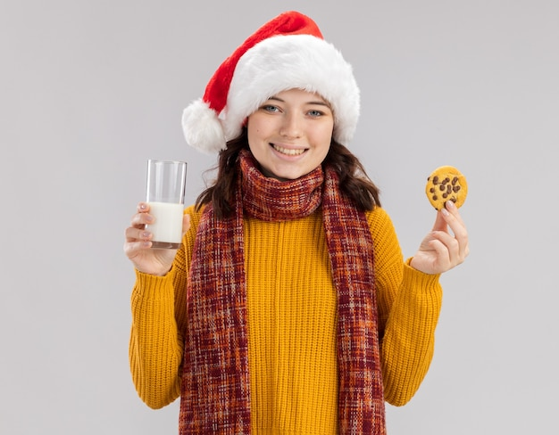 Smiling young slavic girl with santa hat and with scarf around neck holding glass of milk and biscuits isolated on white wall with copy space