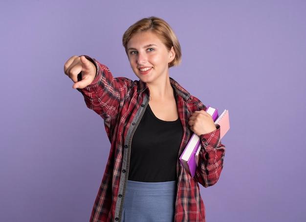 Sorridente giovane studentessa slava tiene libro e taccuino e punta in avanti