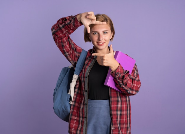 Sorridente giovane studentessa slava che indossa una cornice di gesti dello zaino con le mani che tengono libro e taccuino