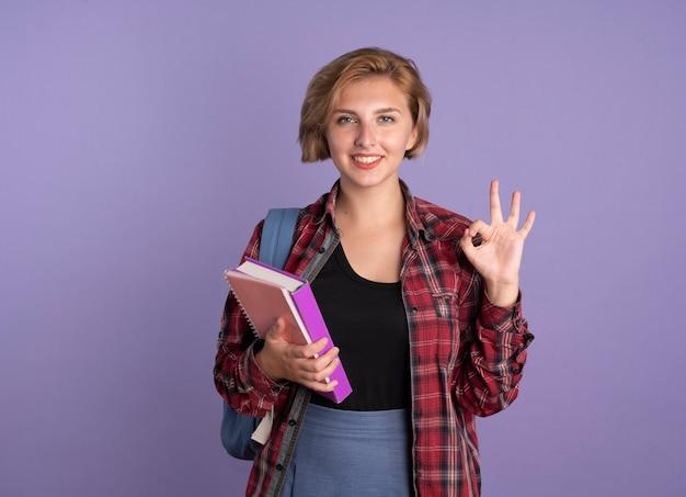 배낭을 입고 웃는 젊은 슬라브 학생 소녀 보유 책 및 노트북 제스처 확인 손 기호