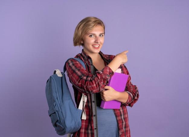 Sorridente giovane studentessa slava che indossa uno zaino tiene un libro e un taccuino puntato a lato
