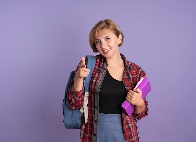 La giovane studentessa slava sorridente che indossa lo zaino tiene i punti del libro e del taccuino alla macchina fotografica