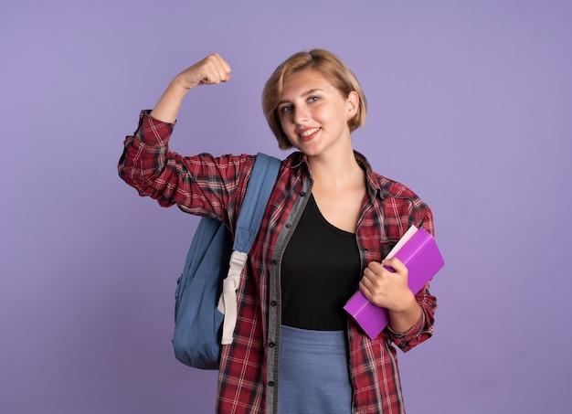 Sorridente giovane studentessa slava che indossa uno zaino tende i bicipiti tiene un libro e un taccuino