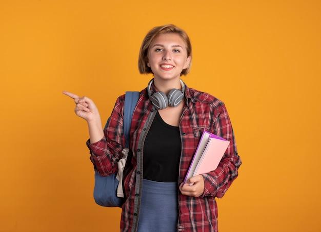 책과 측면을 가리키는 노트북을 들고 배낭을 착용하는 헤드폰으로 웃는 젊은 슬라브 학생 소녀