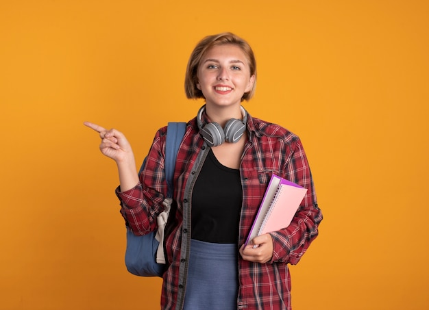 Sorridente giovane studentessa slava con le cuffie che indossa uno zaino con in mano un libro e un taccuino rivolto a lato