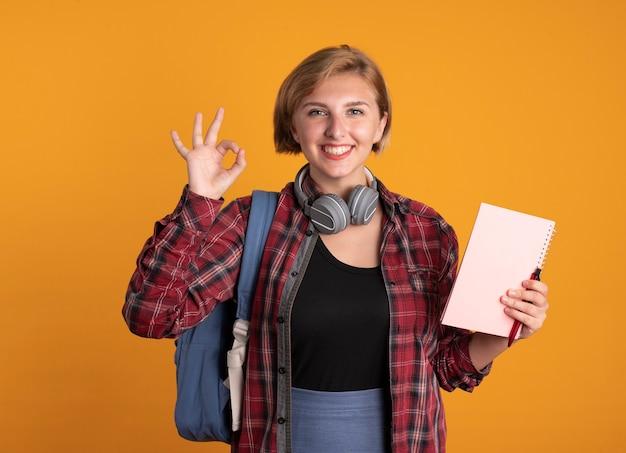 배낭을 착용하는 헤드폰으로 웃는 젊은 슬라브 학생 소녀 보유 노트북 및 펜 제스처 확인 손 기호