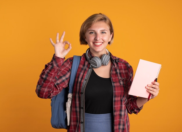 Sorridente giovane studentessa slava con le cuffie che indossa lo zaino tiene il taccuino e i gesti della penna ok segno della mano Foto Gratuite