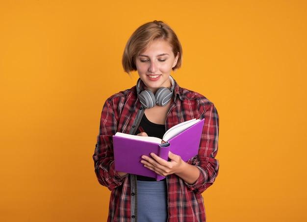 배낭을 착용하는 헤드폰으로 웃는 젊은 슬라브 학생 소녀가 펜으로 책에 씁니다.