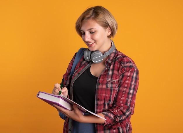 バックパックを着たヘッドフォンで笑顔の若いスラブ学生の女の子がペンでノートに書き込みます