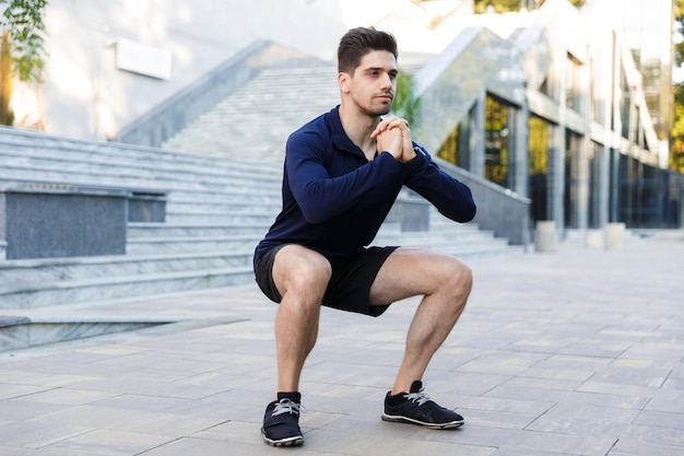 Smiling young sportsman doing squats exercises outdoors