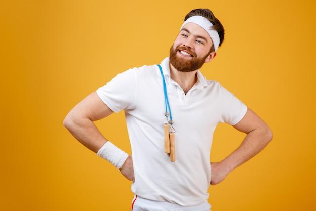 Улыбающийся молодой спортсмен, держа скакалку
