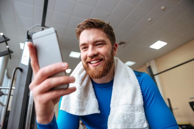 電話でチャットのジムで若いスポーツマンを笑っています。