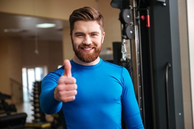 笑顔の若いスポーツマンは親指ジェスチャーを作る