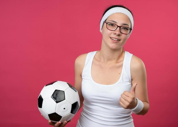 ヘッドバンドを身に着けている光学メガネで若いスポーティな女の子の笑顔